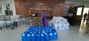 A frontliner of QCGH receives the PPE and food packs donated by PhilKOFA and its partners